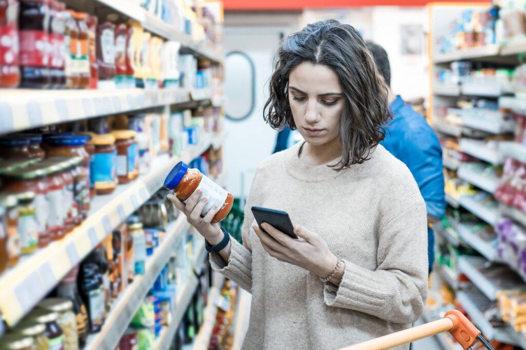 Tijdens het boodschappen doen checkt dit meisje bespaartips op haar telefoon